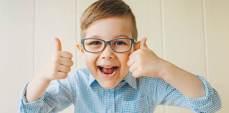 a young boy with nice glasses giving two thumbs-up